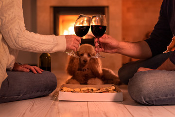Young couple have romantic dinner with pizza and wine over fireplace background. Romantic concept .