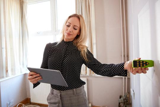 Female Realtor With Digital Tablet Measuring Room With Laser Measure