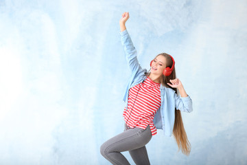 Beautiful young woman dancing on color background