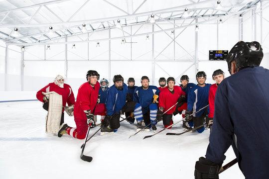 Group of ice hockey players kneeling on ice rink