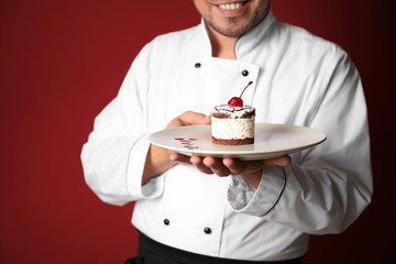 Male chef with tasty dessert on color background, closeup