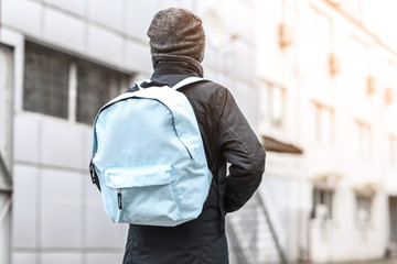 Cute little schoolboy with backpack outdoors