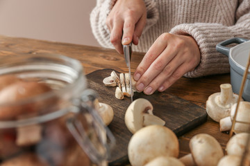 Woman cutting raw mushrooms on wooden board