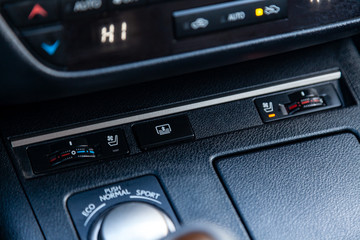 The central control console on the panel inside the car close-up buttons climate control and heated seats in black and gray.