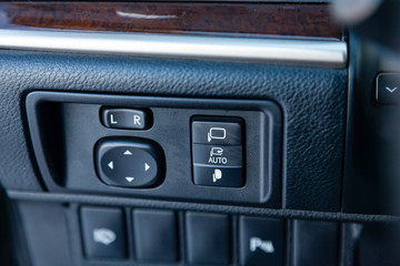 The buttons for controlling the mirrors electric drive on the center console of the instrument panel inside the car are of modern design in black with white signs and symbols.