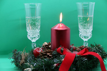 Two glasses of champagne, a red candle, a wreath on a green background.