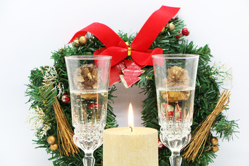 Two glasses of champagne, a golden candle, a wreath on a white background.