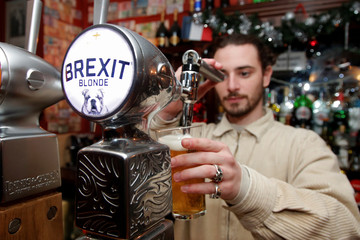 Thibault, barman at the Cricketer English Pub, serves a Brexit draft beer in Paris