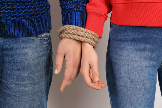 Couple with tied together hands on light background. Concept of addiction