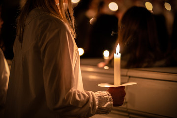 People handling candles in the hands. Christmas and lucia holidays in Sweden