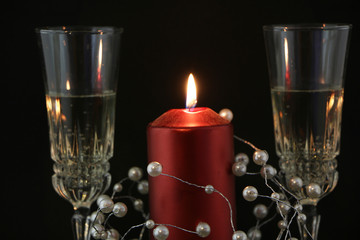 Two glasses of champagne, red candle, a wreath on a black background