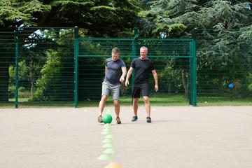 Mature men kicking ball on court