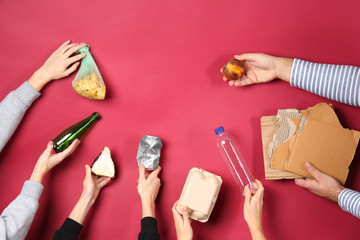 Many hands with different types of garbage on color background. Ecology concept Wall mural