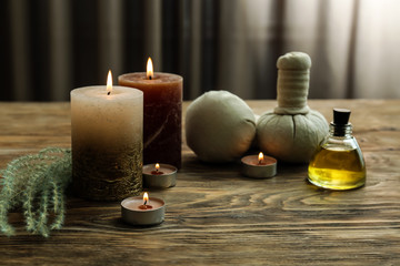 Beautiful spa composition with burning candles, essential oil and herbal bags on wooden table