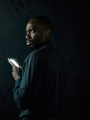Studio shot of young serious black African man thinking while talking on mobile phone against black studio background