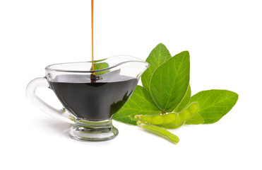 A bowl of soy sauce with plant. Isolated on white background