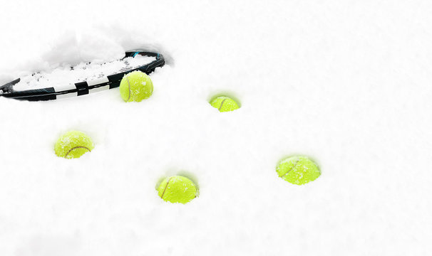Tennis balls and racket on white snow winter background. Merry Christmas and Happy New year concept with tennis balls and play. Close up, sport lifestyle, funny. Isolated horizontal