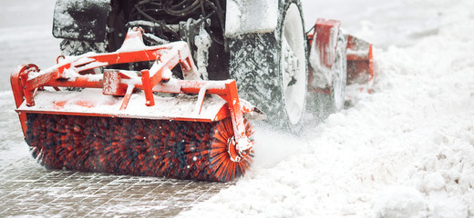 City service cleaning snow , a small tractor with a rotating brush clears a road in the city park from the fresh fallen snow on winter day, brush - close-up.