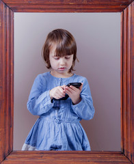 Using mobile phone as symbol of nothing seen, heard, said at the same time. Conceptual photo of little child girl with smart phone.