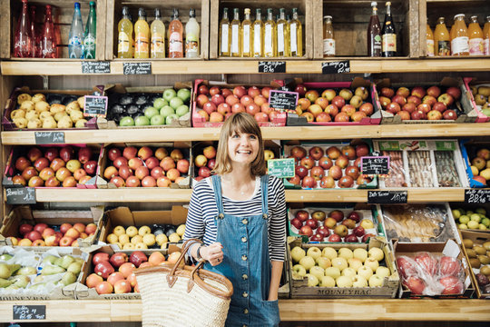Smiling young woman in fruit and vegetable store