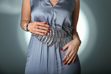 Young woman in dress wearing stylish accessories on grey background