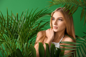 Portrait of beautiful woman with tropical leaves on color background