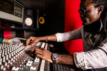 African man sound engineer with headphones at work. side view