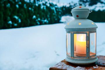 Lantern in winter snowy garden.