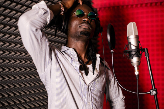 African man in a recording Studio. The guy is a singer at a rehearsal with a microphone. Music school