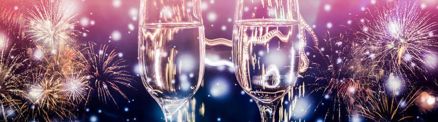 Colorful fireworks and two glasses of wine fizz champagne with bubbles close-up on the falling snow background.