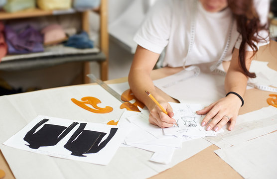 Female designer drawing pencil sketches of clothing sitting at big table with flat paper patterns, measuring ruler and curves on blurred background of tailor design studio interior.