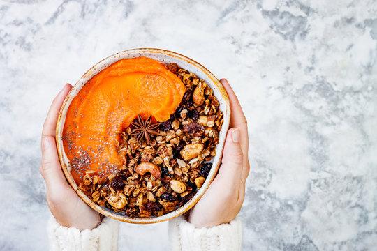 Woman in woolen sweater holding bowl with cinnamon granola, coconut yogurt, chia seeds and pumpkin puree. Healthy vegan, vegetarian breakfast smoothie bowl
