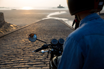 Motorcyclist on ramp to beach at sunset