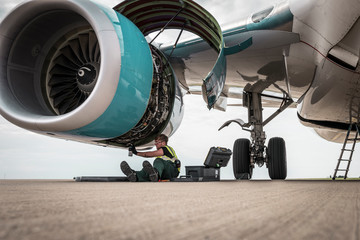 Man working on airplane engine on runway