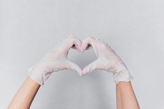 Heart made of white medical gloves isolated on grey background-Image.