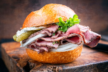 Foto auf AluDibond Fastfood Traditional sliced cold cuts roast beef sandwich with onion, gherkin and remoulade offered as closeup on an old wooden board