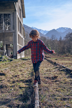 Boy balancing on old railways near building and mountains