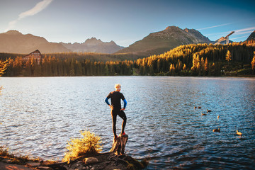 Man standing by lake and looking at autumn morning nature in mountains. strbske plesko, slovakia, High Tatras
