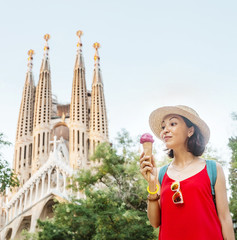 Young woman tourist in front of the famous Sagrada Familia landmark at evening time in Barcelona