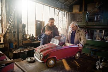 Multi generation family in aDIY workshop to repair a pedal car