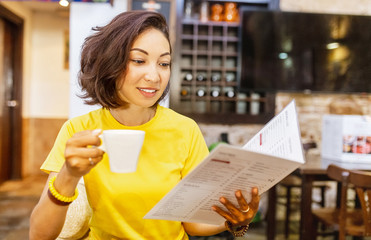 Woman drinking coffee and reading menu in cafe