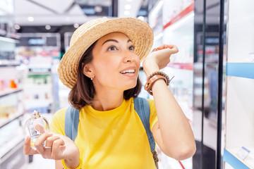 Happy Woman tries new perfume fragrances in perfume shop