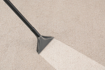 Removing dirt from carpet with vacuum cleaner in room