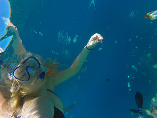 Young girl diving in a blue clean water