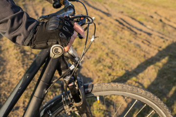 The hand of a cyclist in a glove holds the handlebars. Bicycle equipment intended for long journeys. The life of a traveler, on two wheels on a road-free.