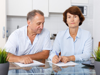 Positive mature couple at kitchen table filling up documents together