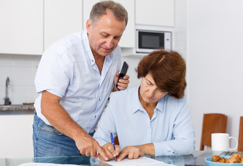 Mature couple  at table in home kitchen, woman filling up documents