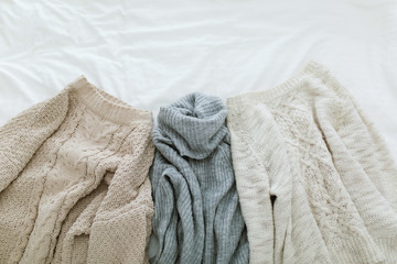 Flat lay autumn and winter fashion photography. Stylish women outfit. Brown knitted sweaters and gray turtleneck. Trendy comfy clothes