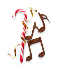 Composition with wooden music notes and candy cane on white background, top view