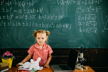 Keep calm and welcome back to school. Little girl is back to school standing at chalkboard in school classroom